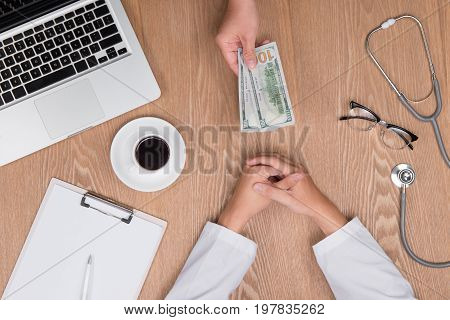 Cropped image of young doctor in white coat talking money from his patient while working in office
