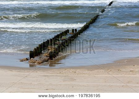 Double wooden breakwaters by the Baltic sea as seen at the shore of a sandy beach in Kolobrzeg in Poland