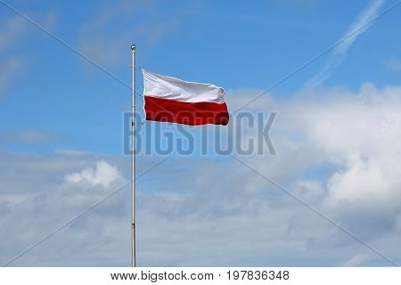 The Polish flag mounted on a high mast is seen on a windy day against the blue sky