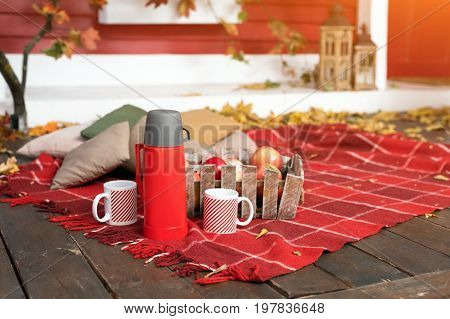 Autumn picnic on the terrace. Red plaid, basket with apples and thermos with hot drink. Veranda of countryside house in autumn season