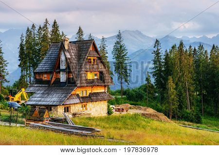 Traditional wooden house in the mountains on a green field Mountains, Poland. Europe