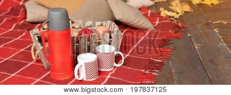 Autumn picnic on the terrace. Red plaid, basket with apples and thermos with hot drink. Veranda of countryside house in autumn season. Banner for website