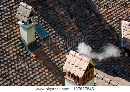 Smoke from the chimney above the roof which is covered by ceramic tiles