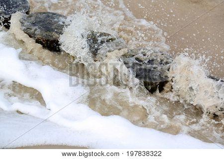 The sea wave splashed over the wooden breakwater. It is seen on the sandy beach of Kolobrzeg in Poland