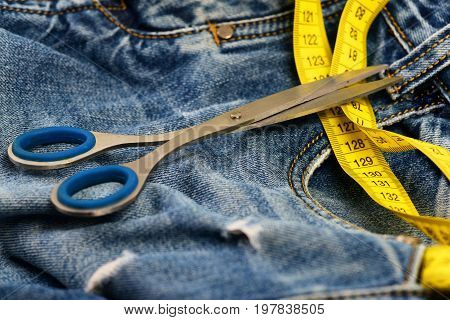 Tailors tools on denim textile. Metal scissors and yellow measure tape on jeans. Jeans belt loops zipper and pocket close up selective focus. Making clothes and design concept.
