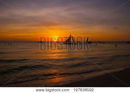 Dramatic Orange Sea Sunset With Sailboats In Tropical Country, Clouds. Philippines, Boracay