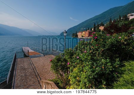 Panoramic view of Como lake shore and Bellano fishing village. Waterfront houses, wooden pier, flowers and mountains. Idyllic italian landscape with small coast town Bellano, Lombardi, Italy.