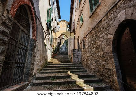 Narrow streets of authentic Bellano fishing village, situated on Como Lake shore. Traditional italian houses, stone steps and arcway  in small town Bellano, Lombardy, Italy.