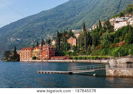 Coastline of Bellano fishing village, situated on Como Lake shore, Lombardy, Italy. Traditional italian houses, mountains and pier in small coast town Bellano.