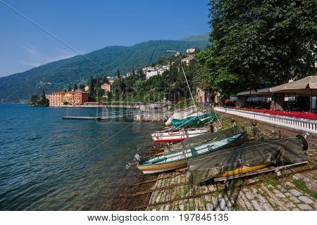 June 13th, 2017 - Lombardy, Italy. Coastline of Bellano fishing village, situated on Como Lake shore. Traditional italian houses, boats and waterfront restaurant in small coast town Bellano.