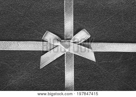 White tied silk ribbon on black wrapping paper as a background
