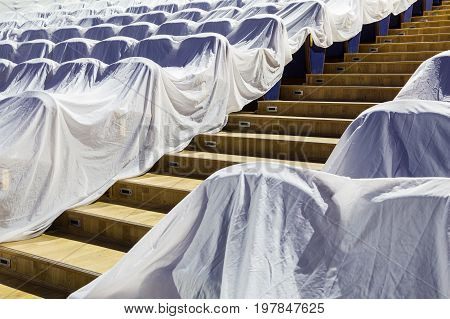 Chairs in the auditorium, covered with a white cloth to protect from dust and dirt.