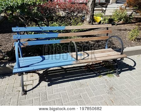 wood park bench half painted blue and half plain wood