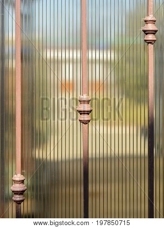 Metal Forged Fence And Sheets Of Translucent Brown Polycarbonate. Blurred Image Of The Summer Garden