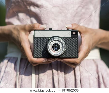 Close up of woman hand holding retro camera. Stock photo