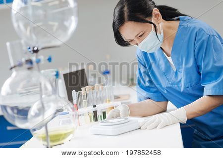 Being accurate. Smart professional nice chemist using electronic scales and weighing chemical powder while working on her research
