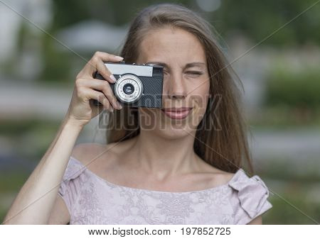 Beautiful woman is taking picture with old fashioned camera, outdoors. Stock photo