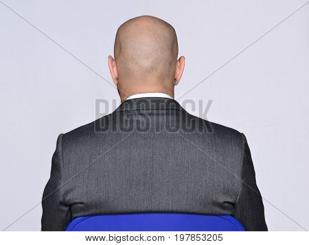 Back view from a bald head businessman siting on white background.