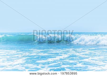 Beautiful tropical sea waves under clear blue sky