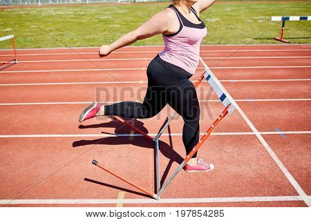 Young plump female running forwards and going to knock hurdle down