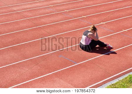 Frustrated chubby woman sitting on stadium racetrack with her head in hands