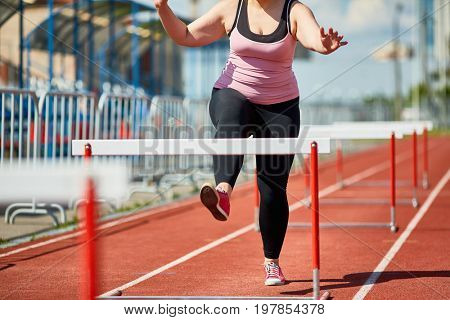 Plump young woman running down stadium racetrack while taking part in hurdle race