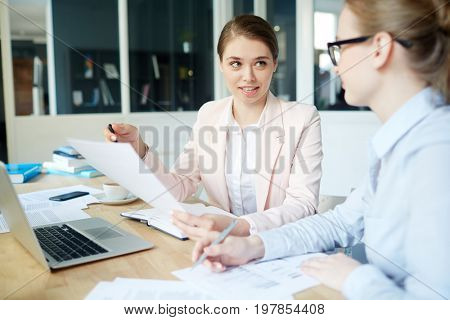 Young economist explaining information to her colleague