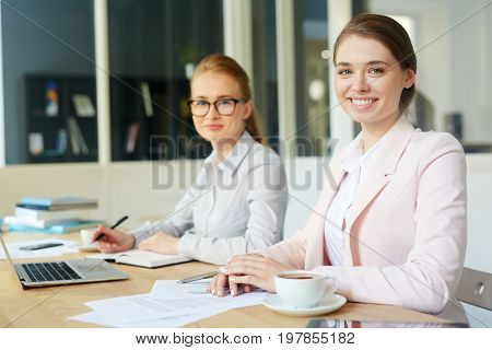 Successful business leader and young employee looking at camera