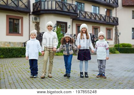 Cute girls and boys in knitwear spending time by their school