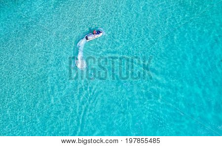 Aerial view. Top view. People are playing a jet ski in the sea.amazing nature background.The color of the water and beautifully bright. Fresh freedom. Adventure day.clear turquoise at tropical beach.