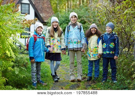 Group of adorable schoolkids standing not far from their school