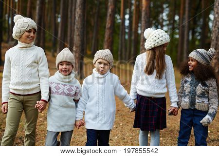 Group of schoolkids having walk in the forest