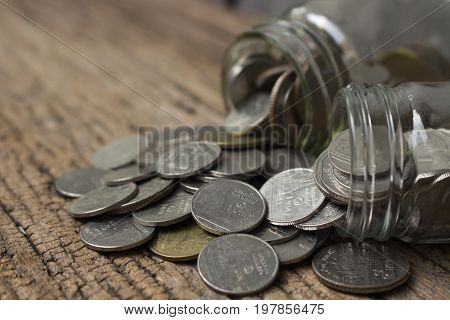 money saving concept for investment,profit,growth business and financial,web or article money management,image of thai coins and glass bottle close up