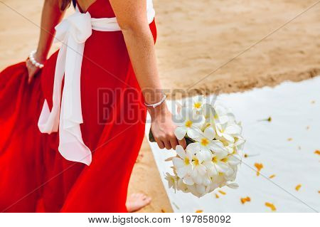 Girl in red fluttering dress holding a white bouquet on the beach before the wedding ceremony. Close-up side view