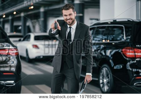 Cheerfull sales manager with new car keys at dealership showroom