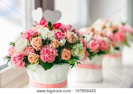 Flower arrangement of white pink and peach roses at the windowsill. Wedding ceremony. Close-up