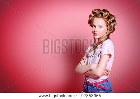 Portrait of a pretty girl teenager with curlers in her blonde hair. Teen style, fashionable teen girl. Studio shot over pink background.