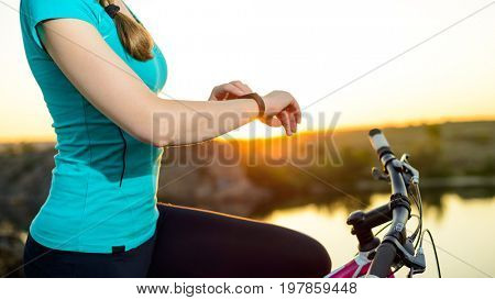 Young Woman Resting with Mountain Bike on the Summer Rocky Trail at Sunset and Using Smartwatch. Closeup of Hands with Smart Watch. Training and Sports Concept.