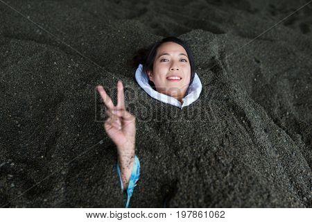 Woman enjoy hot sand bath in Japan
