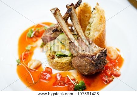 Grilled lamb served on cous-cous with sun dried tomatoes and raisins, goat cheese pastry and smoked tomato and butter sauce