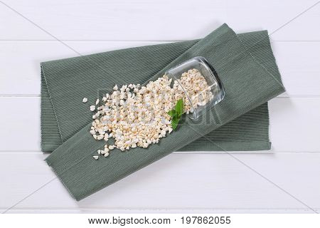 glass of puffed buckwheat spilt out on grey place mat