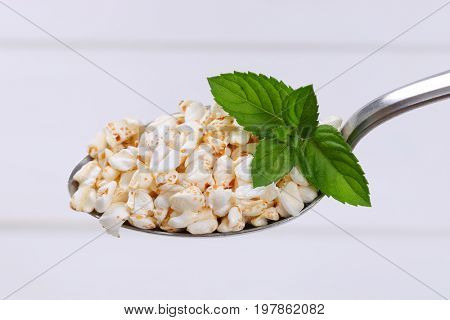 spoon of puffed buckwheat on white wooden background