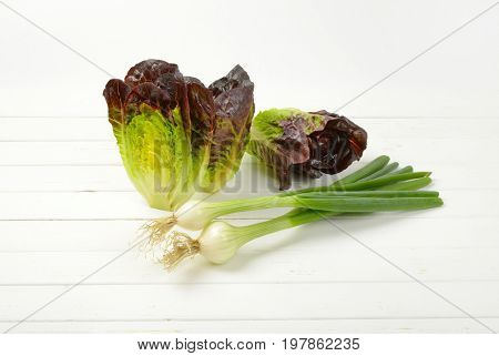 bunch of spring onions and heads of fresh lettuce on white wooden background