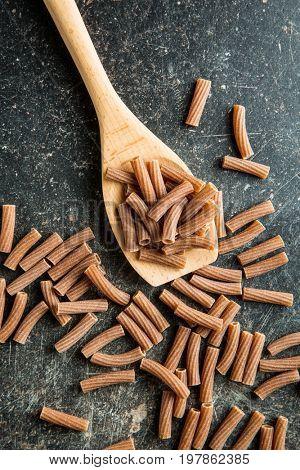 Dried rigatoni pasta on wooden spoon. Dark semolina pasta. Uncooked pasta.