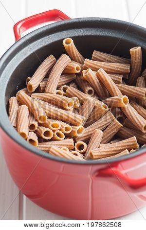 Dried rigatoni pasta in pot. Dark semolina pasta. Uncooked pasta.