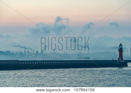 a lighthouse with industrial factory on background,dalian,china.
