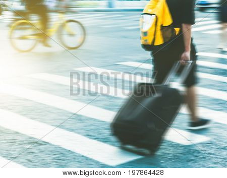 unrecognized pedestrain with suitcase crossing road.