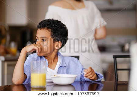 little mixed race boy pondering while eating breakfast with mother in background
