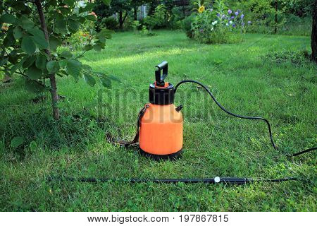 Garden plastic hand pump sprayer with boom on grass. Side view.