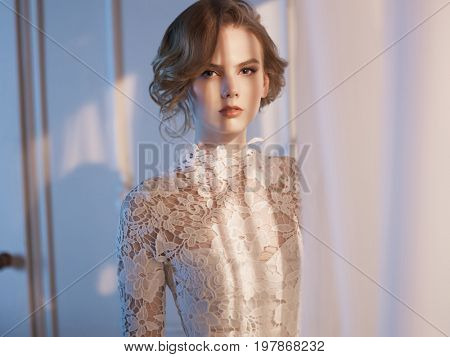 Art fashion portrait of beautiful gorgeous woman in lace dress at the window. Beauty and health. Wedding style. Bridal morning